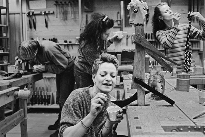 Women in a carpenter«s workshop, creating sculptures.