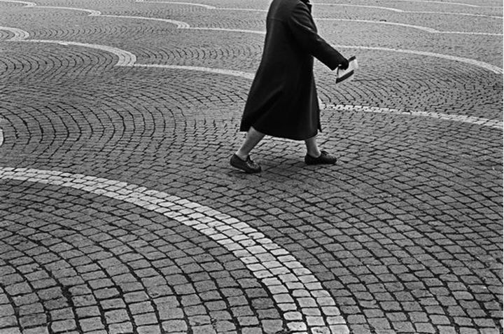 Picture of ideas. Middle-aged woman passing a square with pattern. You do not see her head.