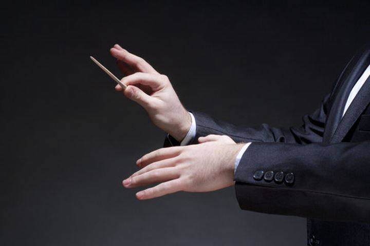 Hands of Conductor with Baton Leading Orchestra