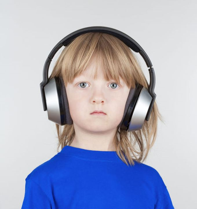 boy with long blond hair listening to music in headphones - isolated on light gray