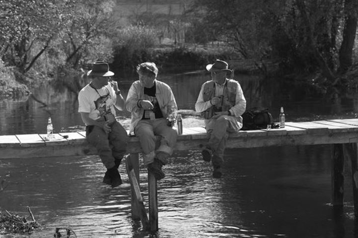 Tre men having outside lunch at riverside. Anglers in Bosnia