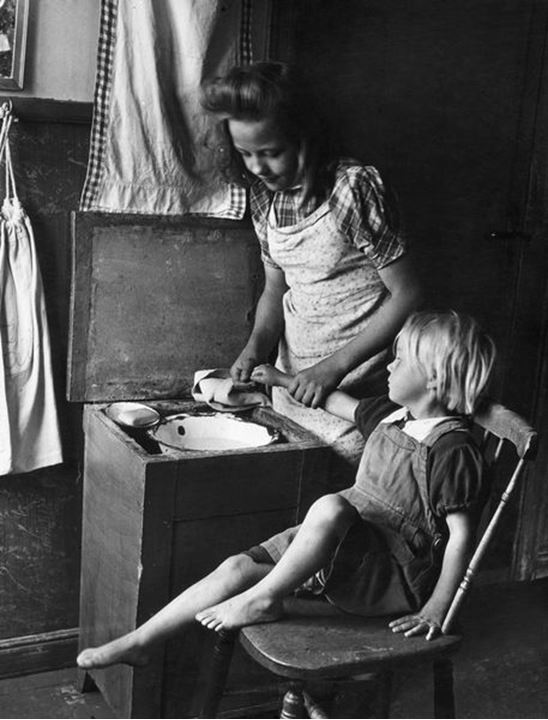 Young girl washing her younger sister´s hands. Dorotea in north Sweden in 1943.