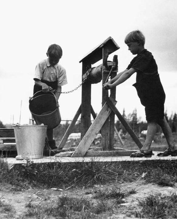 Two boys taking water from the well. Sweden in the 1950´s.
