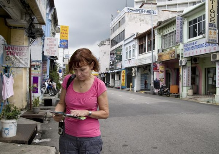 A tourist woman standing in the street looking at a map, Georgetown, Penang  Malaysia