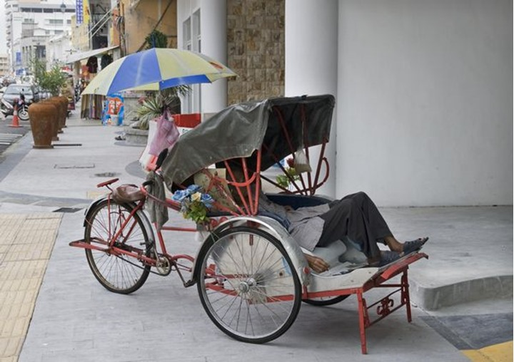 A man taking a nap in a trishaw, Georgetown, Penang Malaysia