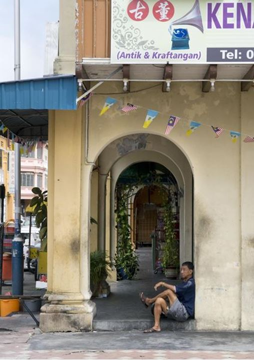 A man resting in the doorstep, Georgetown, Penang, Malaysia