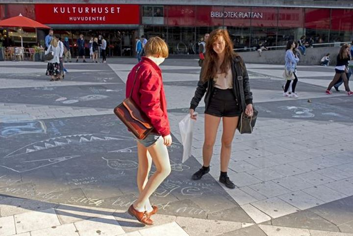 """Two girls making drawings to adress people around in the city of Stockholm """"Plattan"""" Sergels torg"""