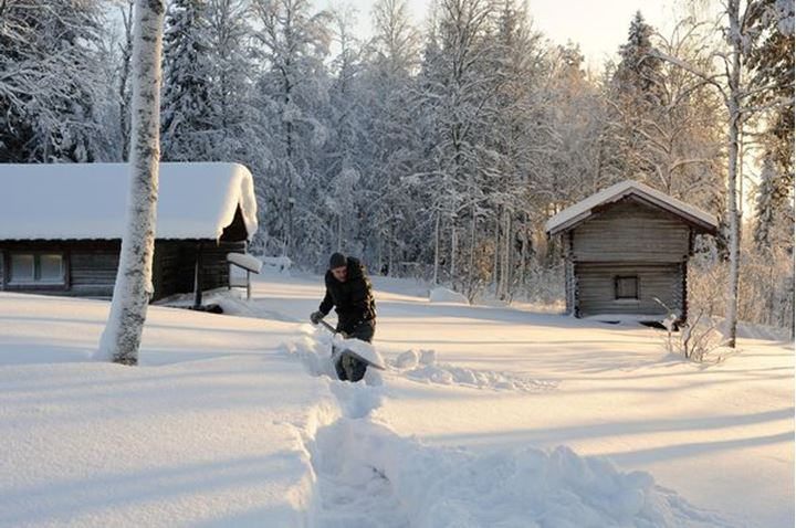 A young man shovelling snow