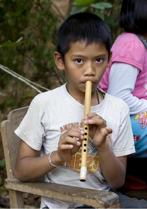 A little Thai boy playing the flute
