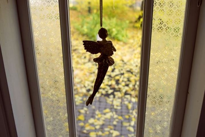 An ornament figrure, angellike, hanging in the window of a pavilion