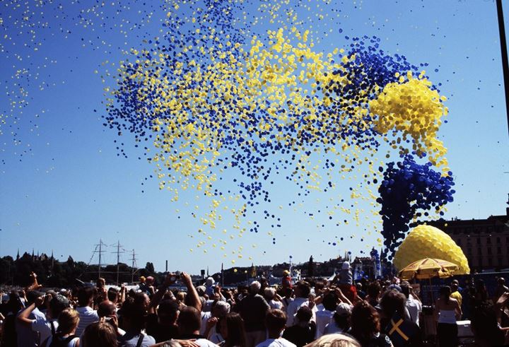 Yellow and blue balloons flying up in the sky. Sweden