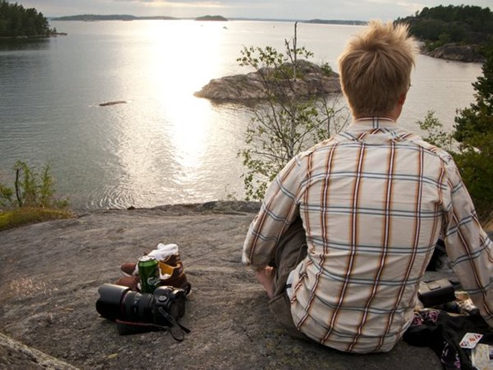 Man on cliff with camera and beer, Stockholm, Sweden