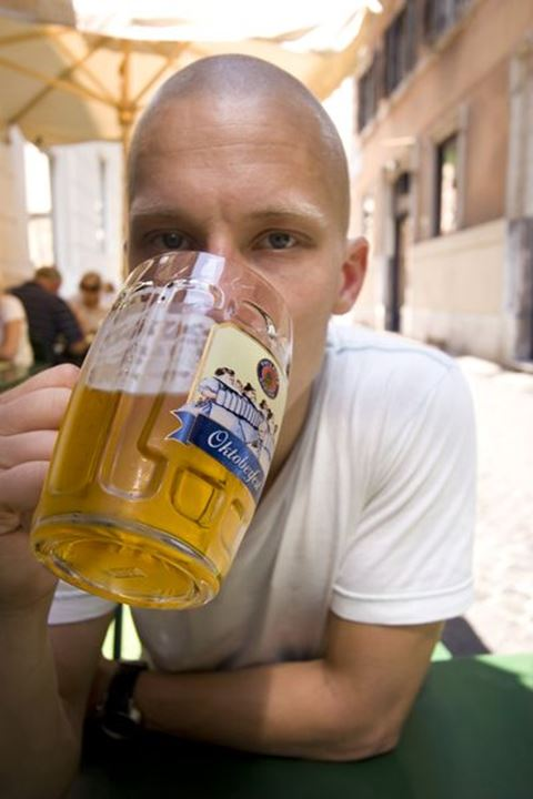 Man drinking beer at outside cafe, rome, italy