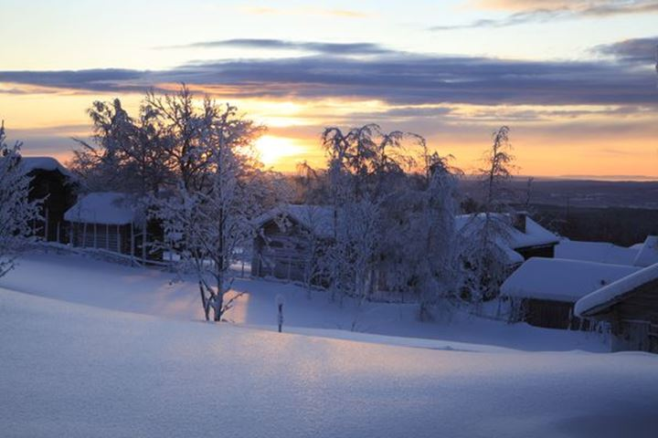 Sunset over snow covered houses, Dalarna, Sweden