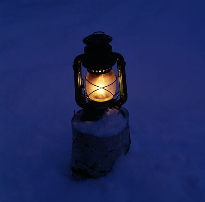 Close-up of a lit lantern on snow