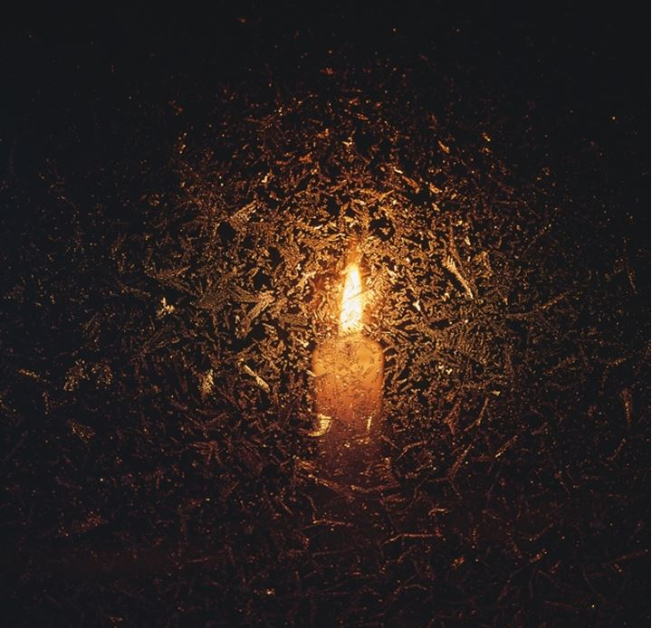 A candle burning behind frozen glass