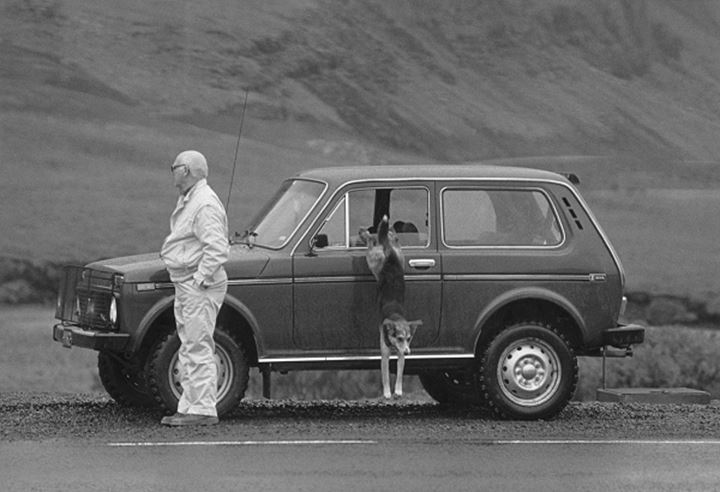 An old man standing near the car and dog jumping