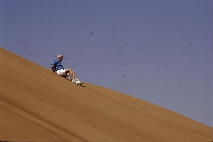 A man slipping down on the sand dune