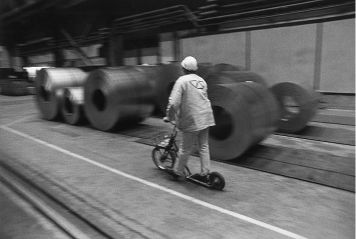 Rear view of a person moving past the rolls of welded steel mesh