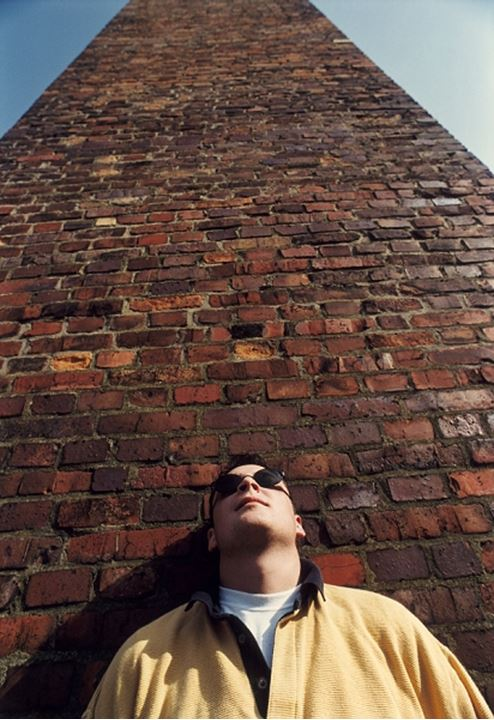 Low angle view of a man standing by the brick wall whilst wearing sunglasses