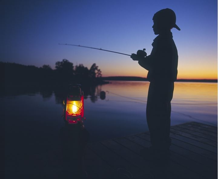 Boy fishing at sea in dusk while standing on dock