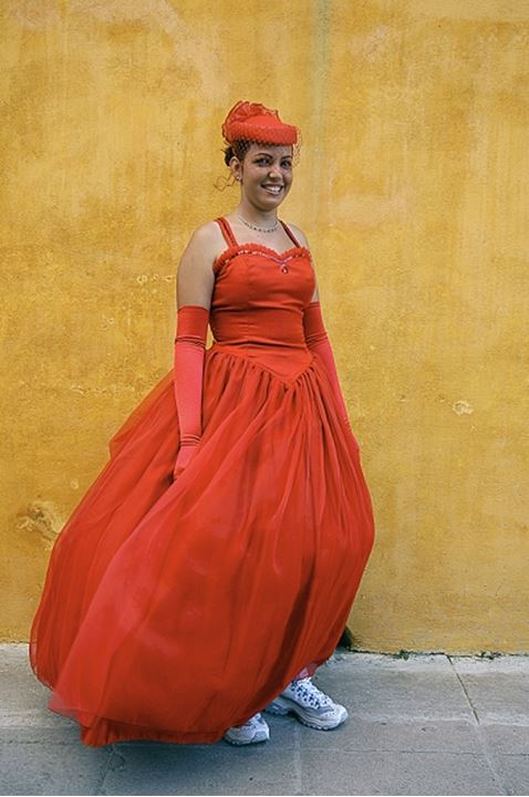 Woman smiling at the camera whilst being dressed in orange