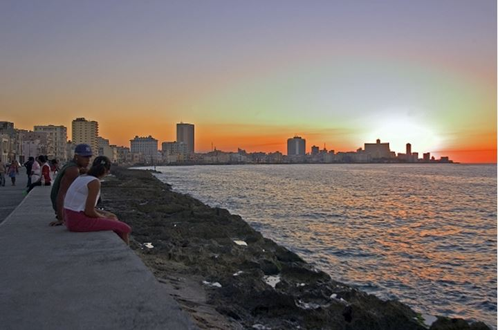 People sitting on wall and watching the sunset in Havana, Cuba