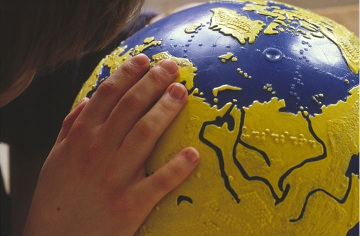 Close-up of a hand reading braille on globe