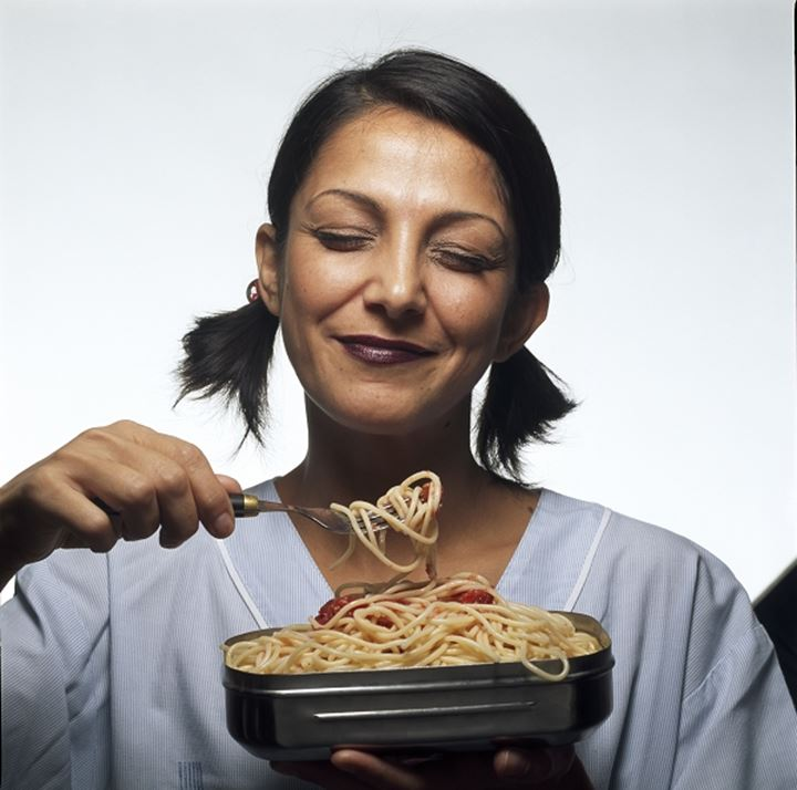 Close-up of a young woman eating noodles with a fork
