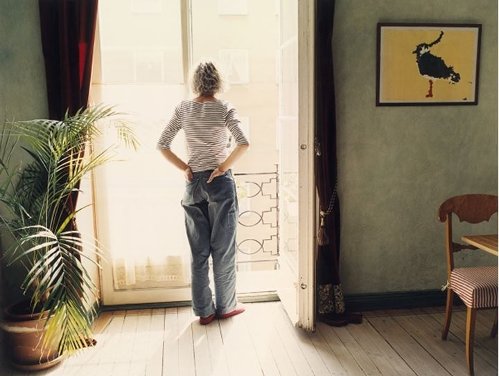 A woman standing by a window