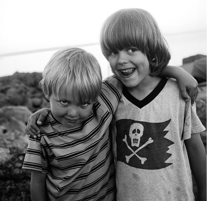 Two small boys standing together by the sea