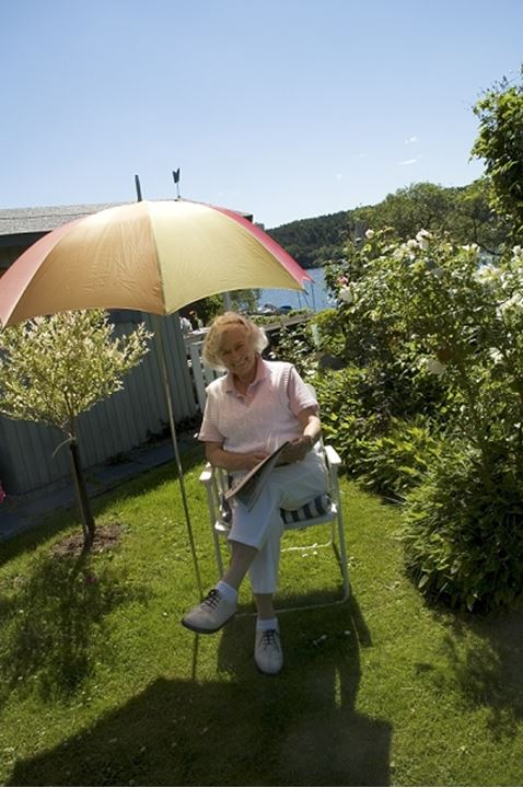 Portrait of a mature woman sitting in a garden, Stockholm, Sweden
