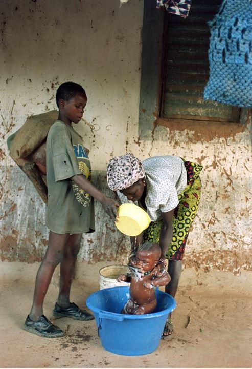 African woman bathing a little baby in a tub in Guinea-Bissau 1994