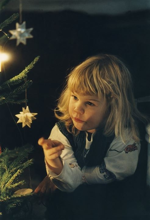 Small girl sitting by the Christmas tree in Stockholm 1995