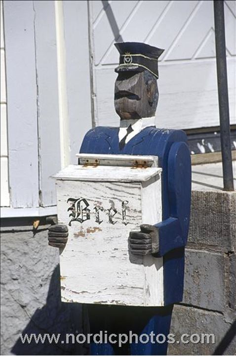 Mailbox held by a wooden postman