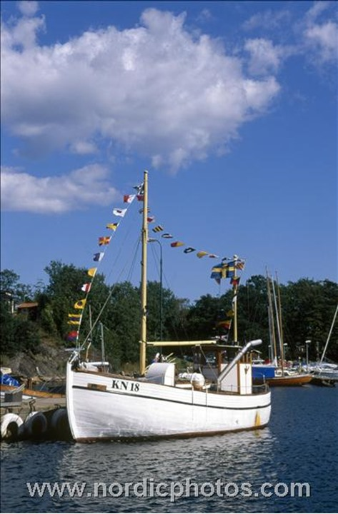 A swedish ship with a lot of small flags on it