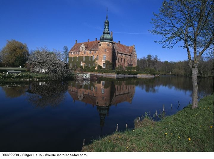 Castle and trees on the shore of river and reflecting in water.Vittskovle Castle.Skane, Sweden