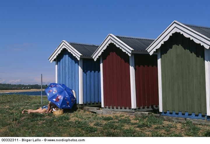Colourful beach huts and people under umbrella