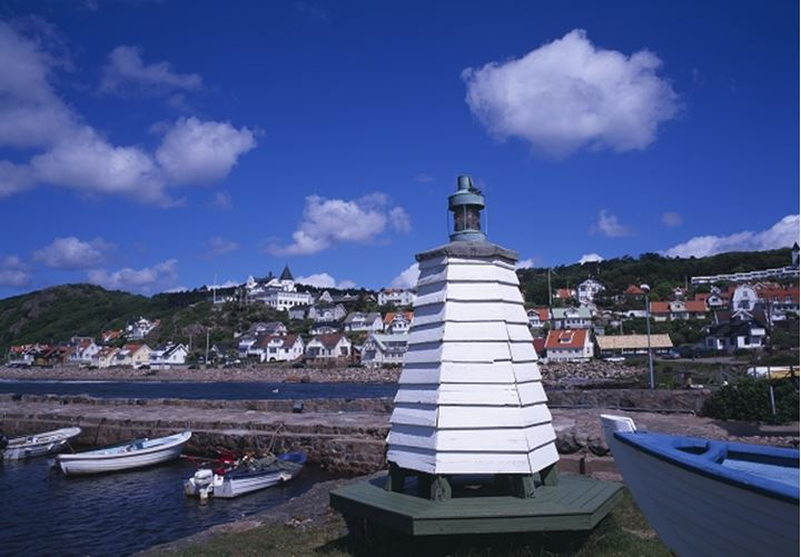 Lighthouse with moored boats and houses