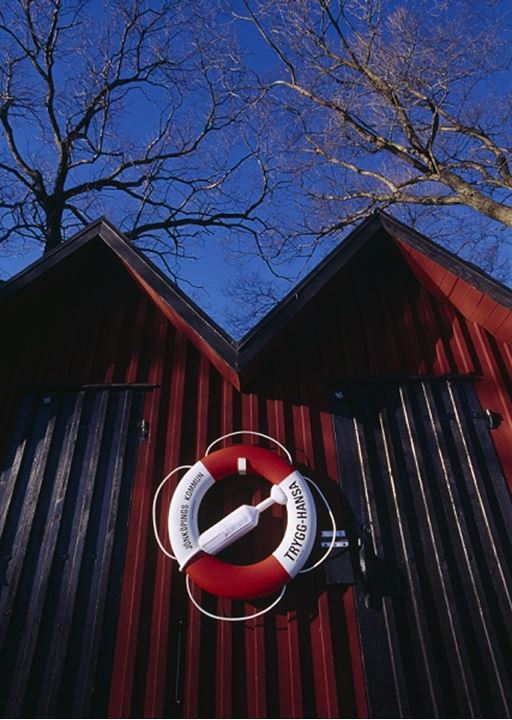 Low angle view of red changing rooms with barren trees