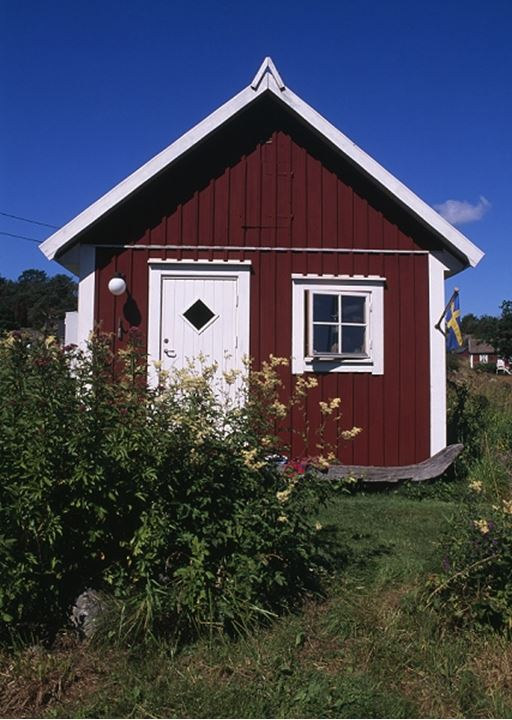 Front view of a red cottage with Swedish flag and plants