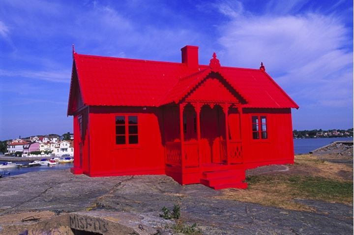 Red house with cloudy sky