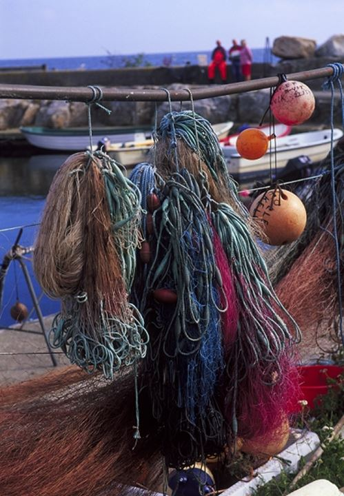 Bunches of ropes and fishing nets hanging on a rod