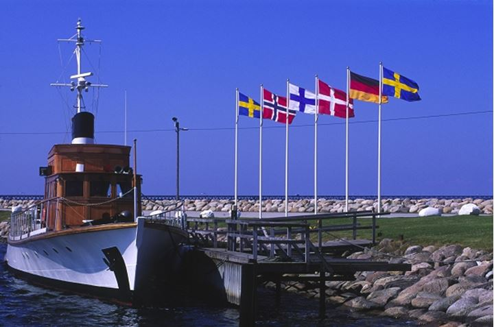 Flags waving on the flag poles by a ship