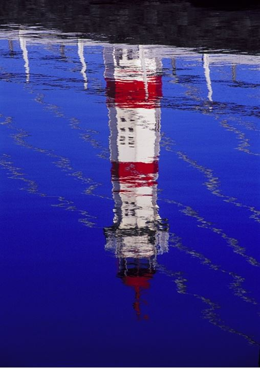 Inverted reflection of a lighthouse in water
