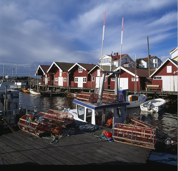 Lobster pots on the wooden dock with boats moored in the river