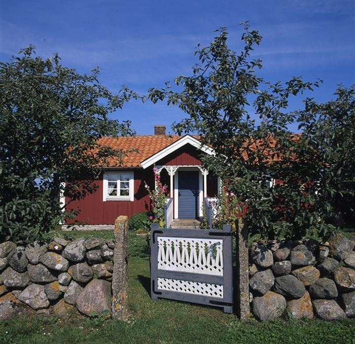 Front view of a cottage with gate and trees
