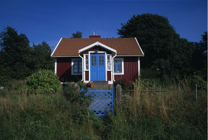 A red cottage with blue doors and gate