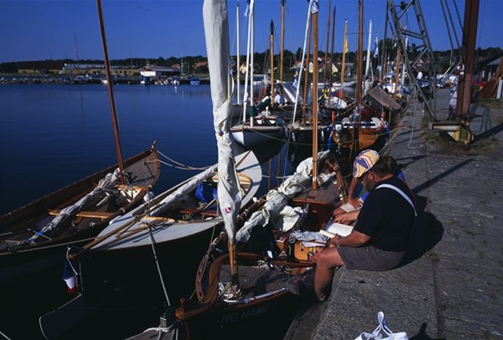Two people sitting by boats on harbour