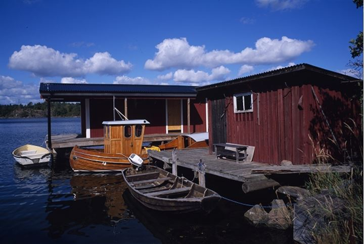 A red cottage with boats and white clouds
